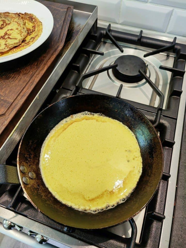 Tilsæt pandekagedej, bag til massen er fast, vend pandekagen og bag færdig til den er gylden